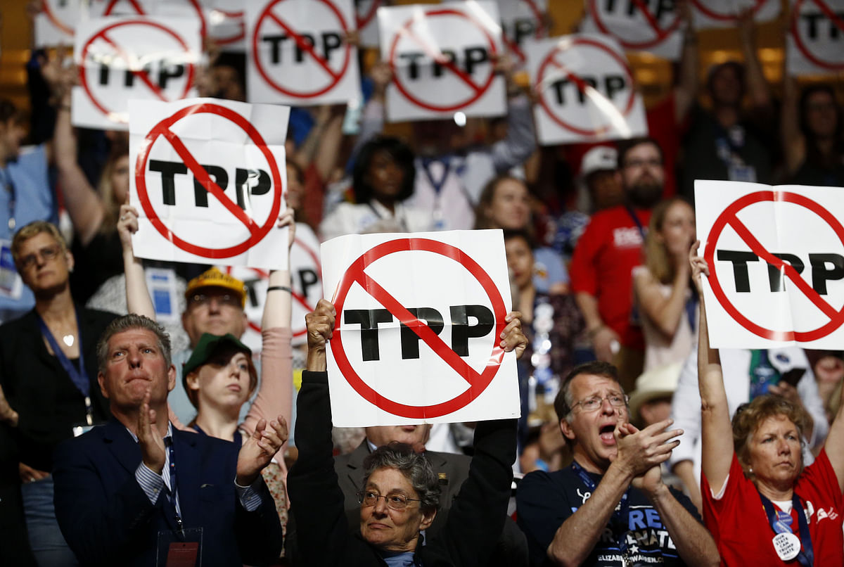 Delegates hold signs against the Trans-Pacific Partnership during the Democratic National Convention in Philadelphia, U.S., on July 25, 2016. (Photographer: Andrew Harrer/Bloomberg)