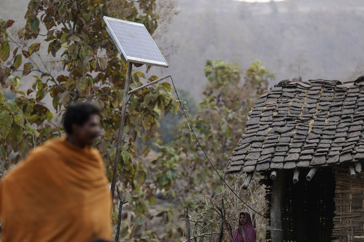 Jurdar Thingya and his wife Kompla Jurdar stand near a broken solar panel outside their home in the village of Bhamana, Maharashtra, on January 18, 2017. (Photographer: Dhiraj Singh/Bloomberg)