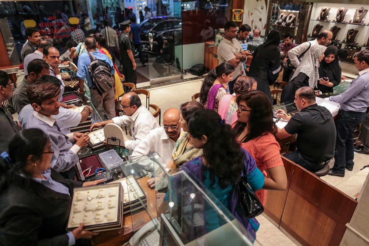 Customers shop for jewelry inside the Dwarkadas Chandumal Jewelers store in the Zaveri Bazaar area of Mumbai, India, to celebrate the Akshaya Tritiya festival on April 21, 2015. (Photographer: Dhiraj Singh/Bloomberg)