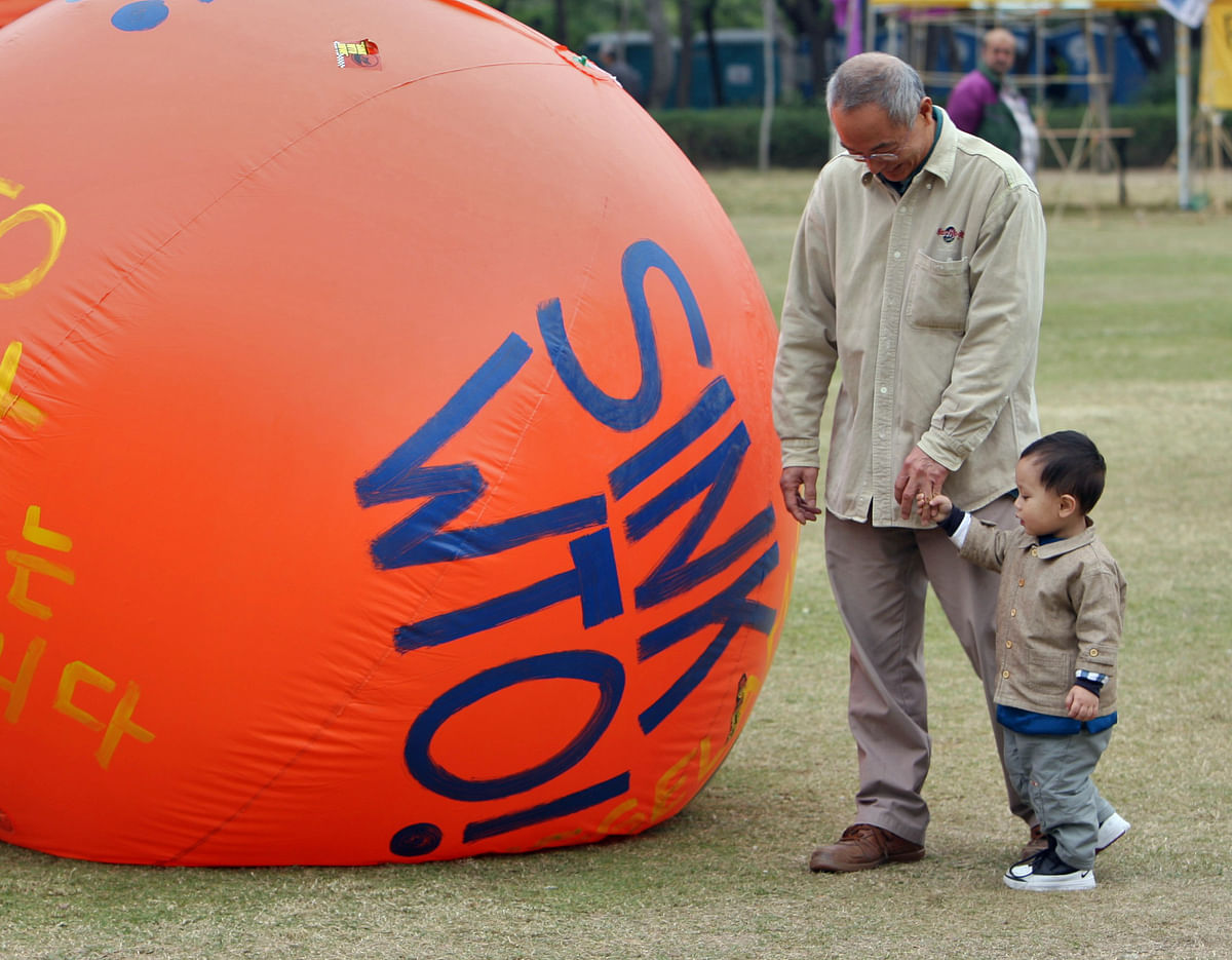 Hong Kong residents walk past balloons which are part of protests against the World Trade Organization's Sixth Ministerial Conference in a park in Hong Kong, China on December 14, 2005. (Photographer: Lucas Schifres/Bloomberg News)