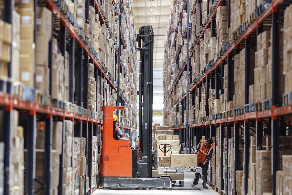 Employees move boxes with a forklift at a warehouse (Photographer: Dhiraj Singh/Bloomberg)