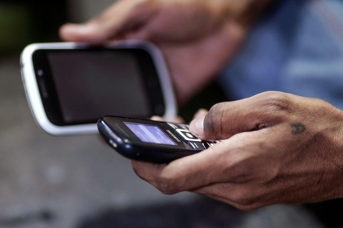 A man uses mobile phones in Mumbai. (Photographer: Dhiraj Singh/Bloomberg)