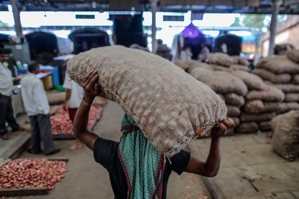 A worker carries a sack of onions on his head at the Vashi Agricultural Produce Market Committee (APMC) wholesale market in Mumbai, India. (Photographer: Dhiraj Singh/Bloomberg)