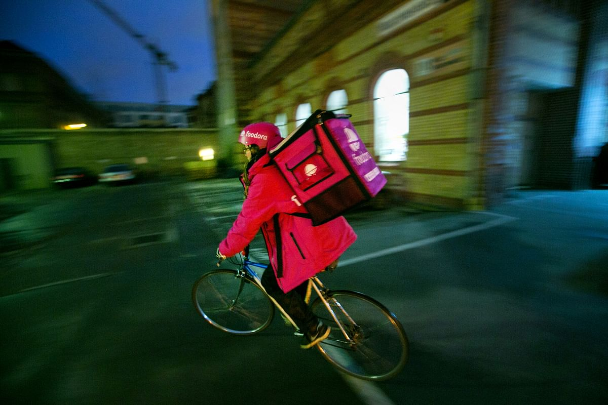 An employee rides a bicycle while carrying a backpack food delivery box outside the headquarters of Foodora, the food courier service operated by Delivery Hero Holding GmbH, in Berlin, Germany. (Photographer: Krisztian Bocsi/Bloomberg)