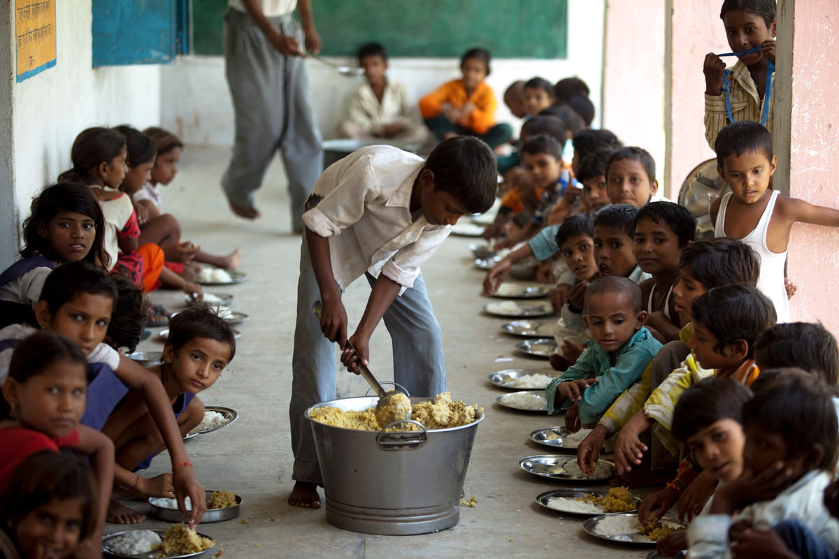 "Children eat at school under the government run scheme of ""Mid Day Meals"" in Laundi, India, (Photographer: Prashanth Vishwanathan/Bloomberg)"