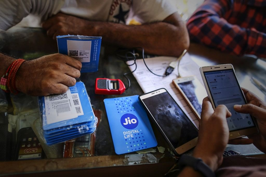 A customer holds a SIM card packet in Mumbai, India. (Photographer: Dhiraj Singh/Bloomberg)