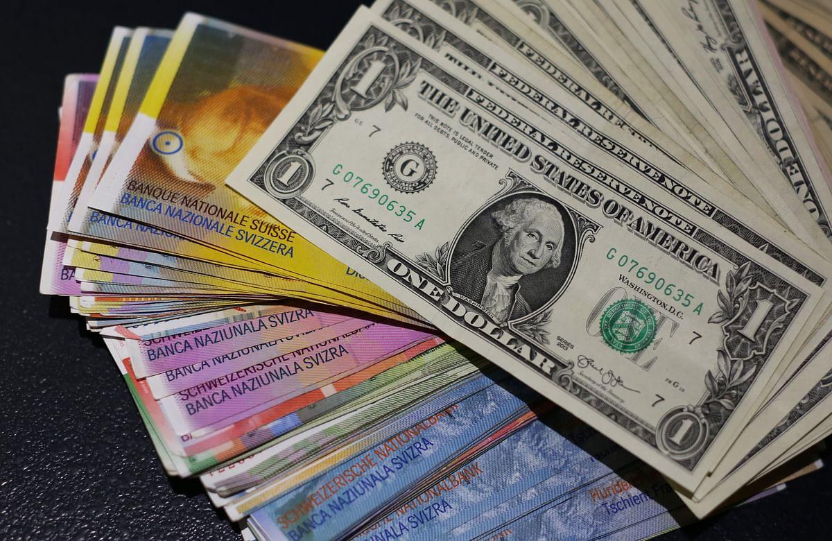 Multiple denomination U.S. dollar bills sit on top of Swiss franc bank notes (Photographer: Chris Ratcliffe/Bloomberg)