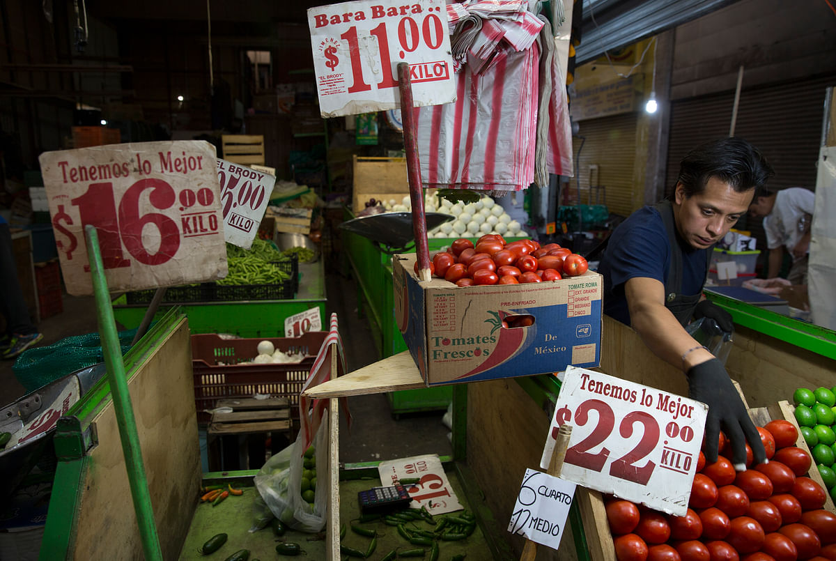 A vendor arranges tomatoes for sale at the Central de Abasto market in Mexico City, Mexico, on  July 28, 2015. (Photographer: Susana Gonzalez/Bloomberg)