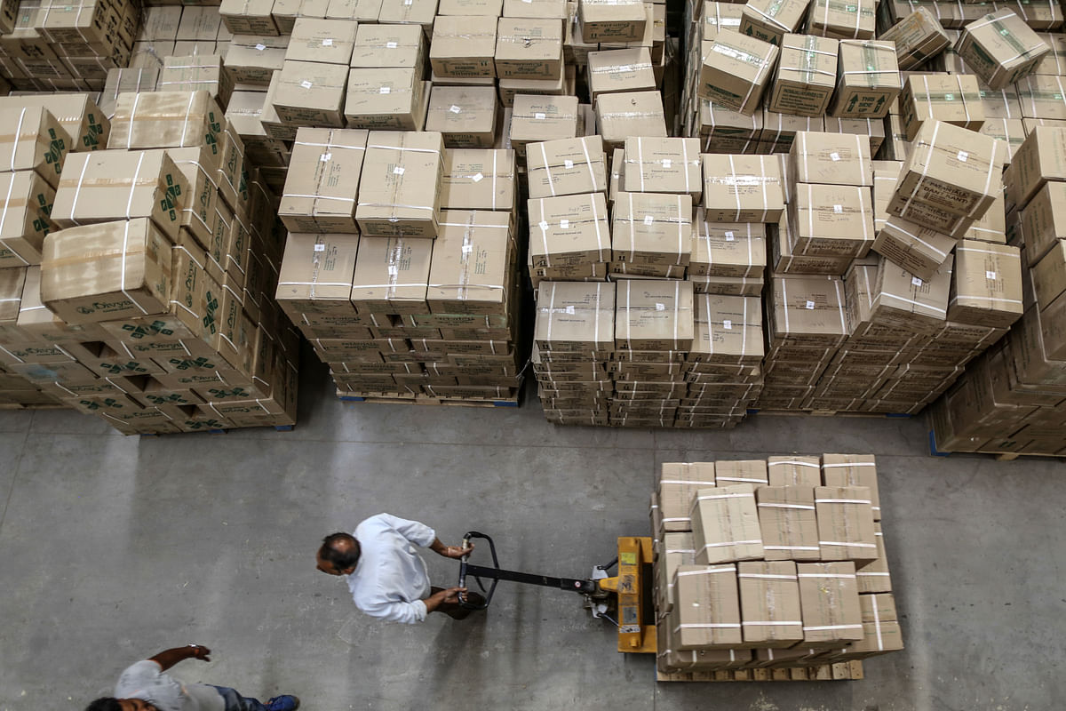 An employee pulls a pallet loaded with boxes inside a warehouse. (Photographer: Dhiraj Singh/Bloomberg)