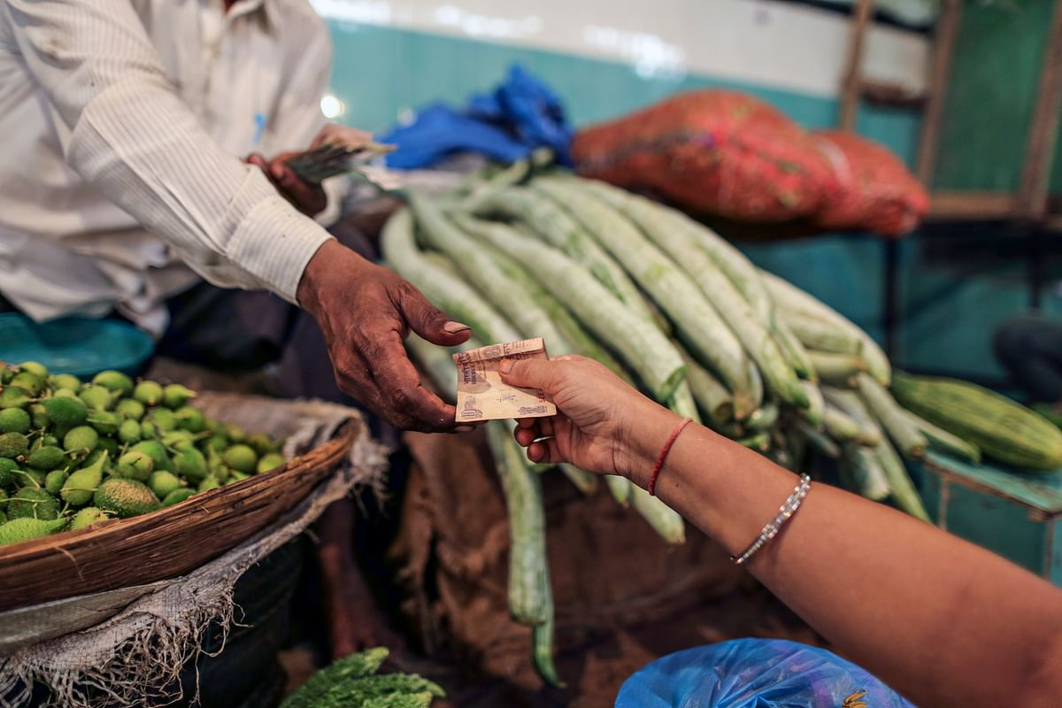 A customer hands over an Indian ten rupee banknote to a vendor at a vegetable market in Mumbai, India. (Photographer: Dhiraj Singh/Bloomberg)