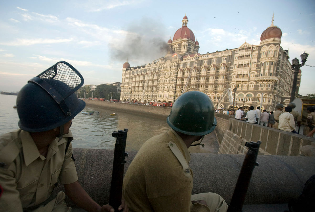 Police personnel watch the Taj Mahal Hotel, set ablaze by terrorists, in Mumbai, India, on November 27, 2008. (Photographer: Prashanth Vishwanathan/Bloomberg)