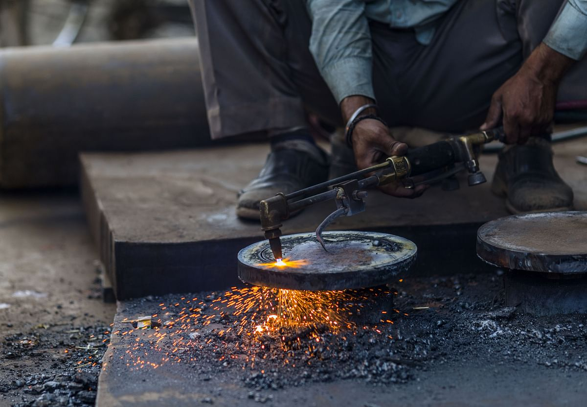 A worker uses a cutting torch in a workshop in a steel and iron market area of New Delhi. (Photographer: Prashanth Vishwanathan/Bloomberg)