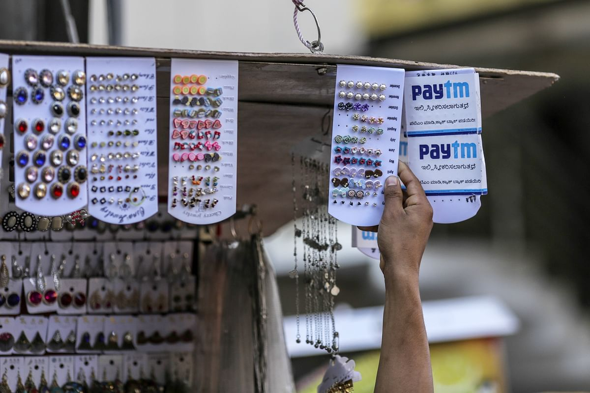 A vendor arranges earrings next to a sign for PayTM online payment method, operated by One97 Communications. (Photographer: Dhiraj Singh/Bloomberg)