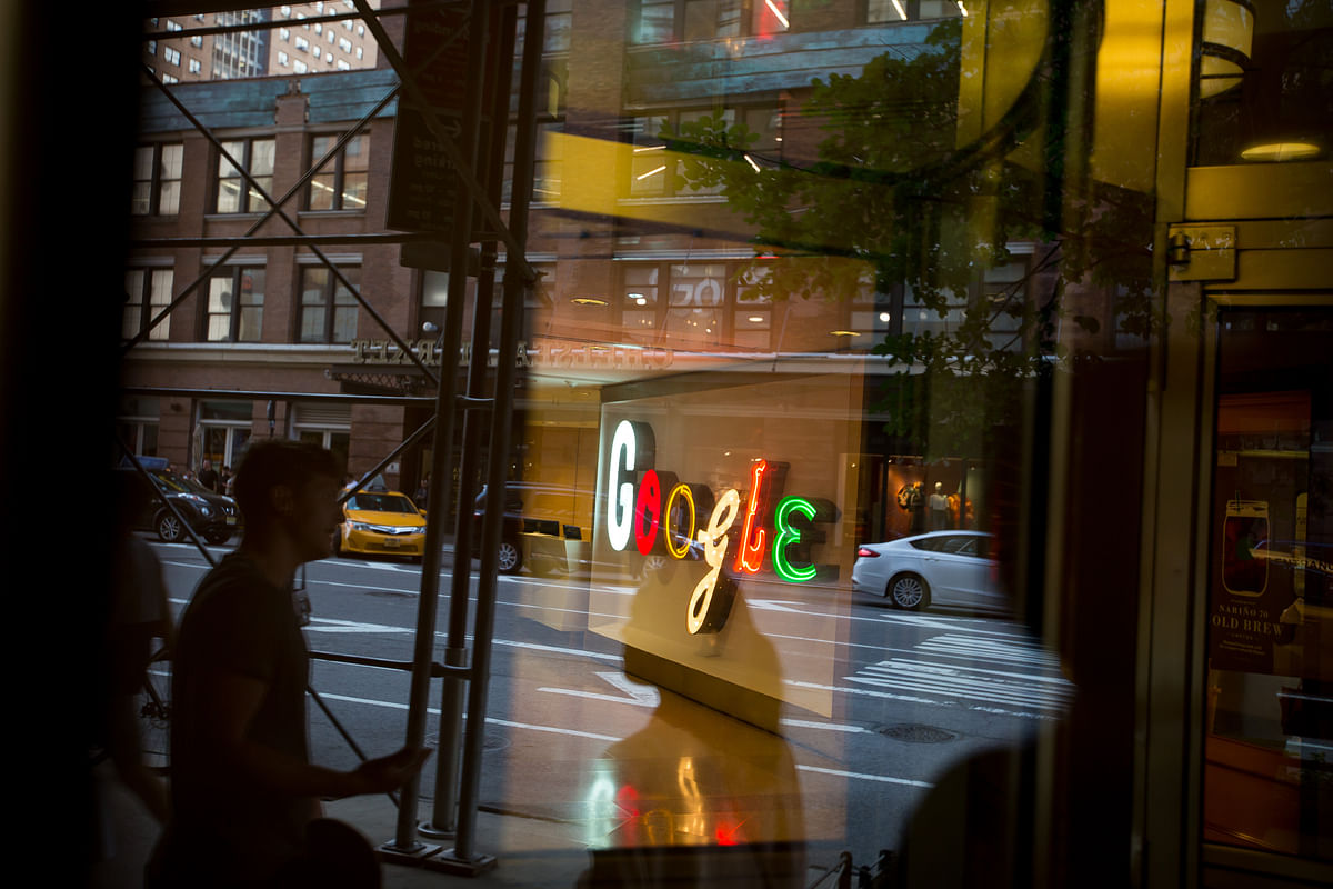 Pedestrians are reflected in a window looking into a lobby of the Google Inc. offices in New York, U.S. (Photographer: Michael Nagle/Bloomberg)