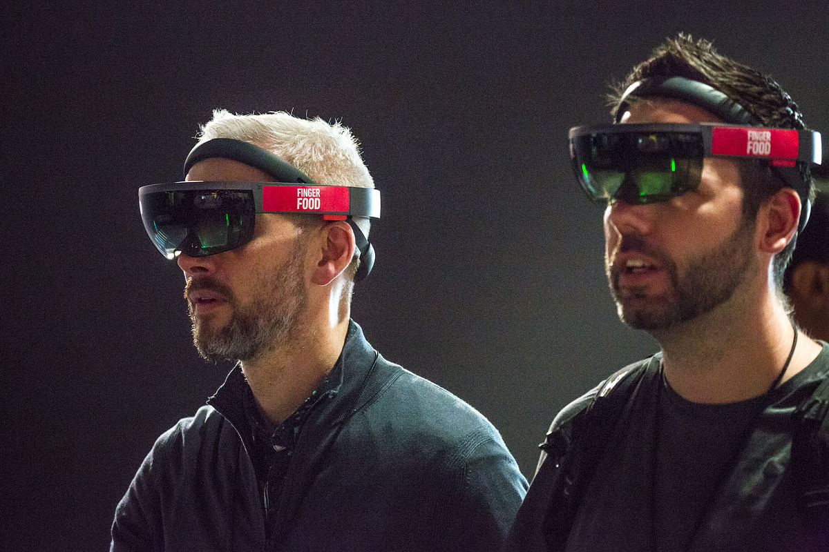 Attendees use Microsoft Corp. HoloLens virtual reality (VR) headsets during a product demonstration by Finger Food Studios at the Microsoft Developers Build Conference in Seattle, Washington, U.S. (Photographer: David Ryder/Bloomberg)