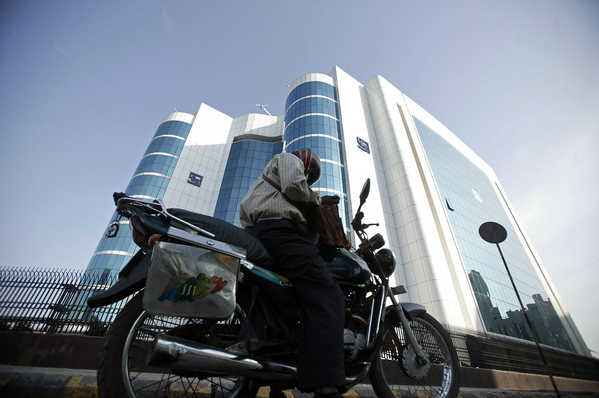 A man stops his motorcycle in front the Securities & Exchange Board of India in Mumbai, India (Photographer: Adeel Halim/Bloomberg News)