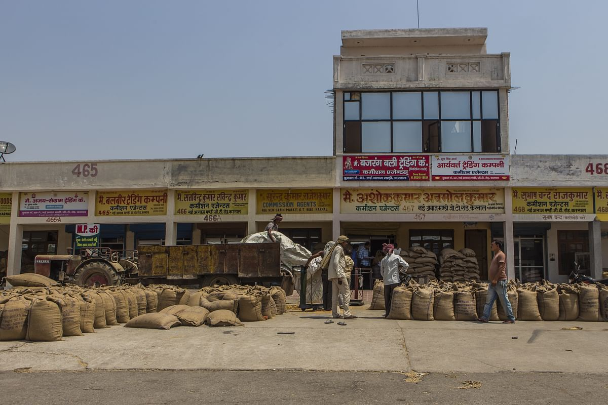 Workers unload wheat from a trailer at a trader's store at the New Grain Market in Karnal, Haryana, India. (Photographer: Prashanth Vishwanathan/Bloomberg)