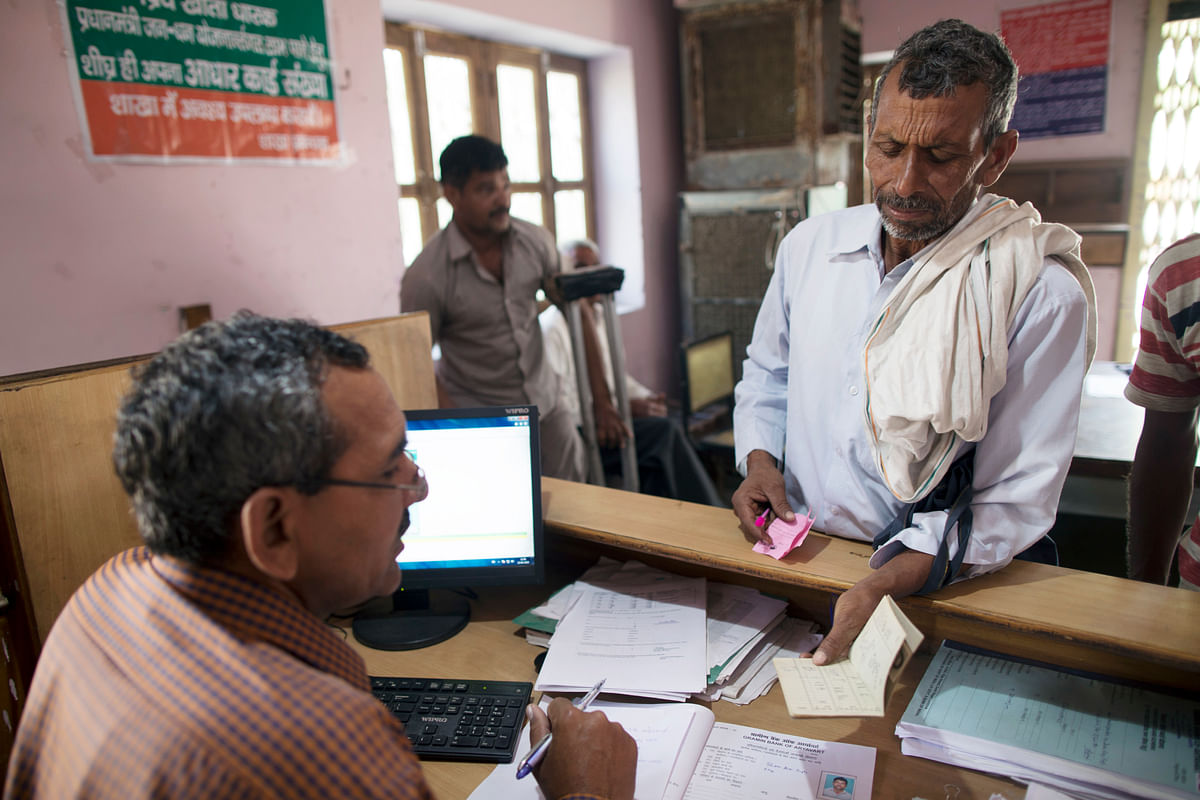 An employee serves a customer inside a branch of Gramin Bank of Aryavat, in the village of Khurana, Uttar Pradesh, India. (Photographer: Prashanth Vishwanathan/Bloomberg)
