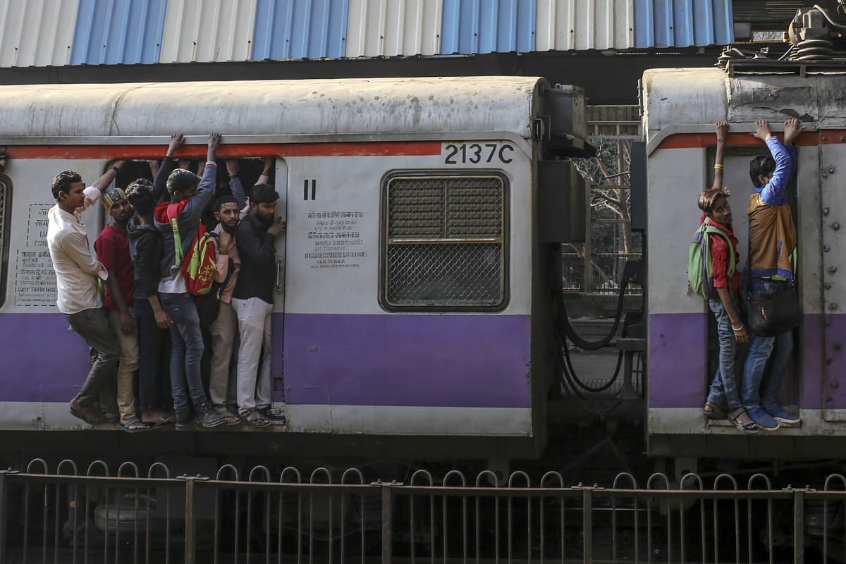 Passengers stand in the doorway, left, and on the side of train carriages as they travel by rail in Mumbai. (Photographer: Dhiraj Singh/Bloomberg)