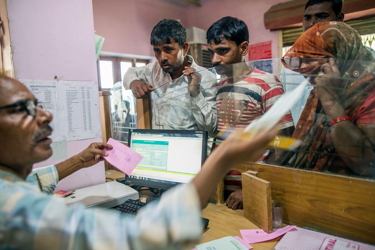 An employee serves customers inside a branch of Gramin Bank of Aryavart, sponsored by Bank of India, in the village of Khurana, Uttar Pradesh, India. (Photographer: Prashanth Vishwanathan/Bloomberg)