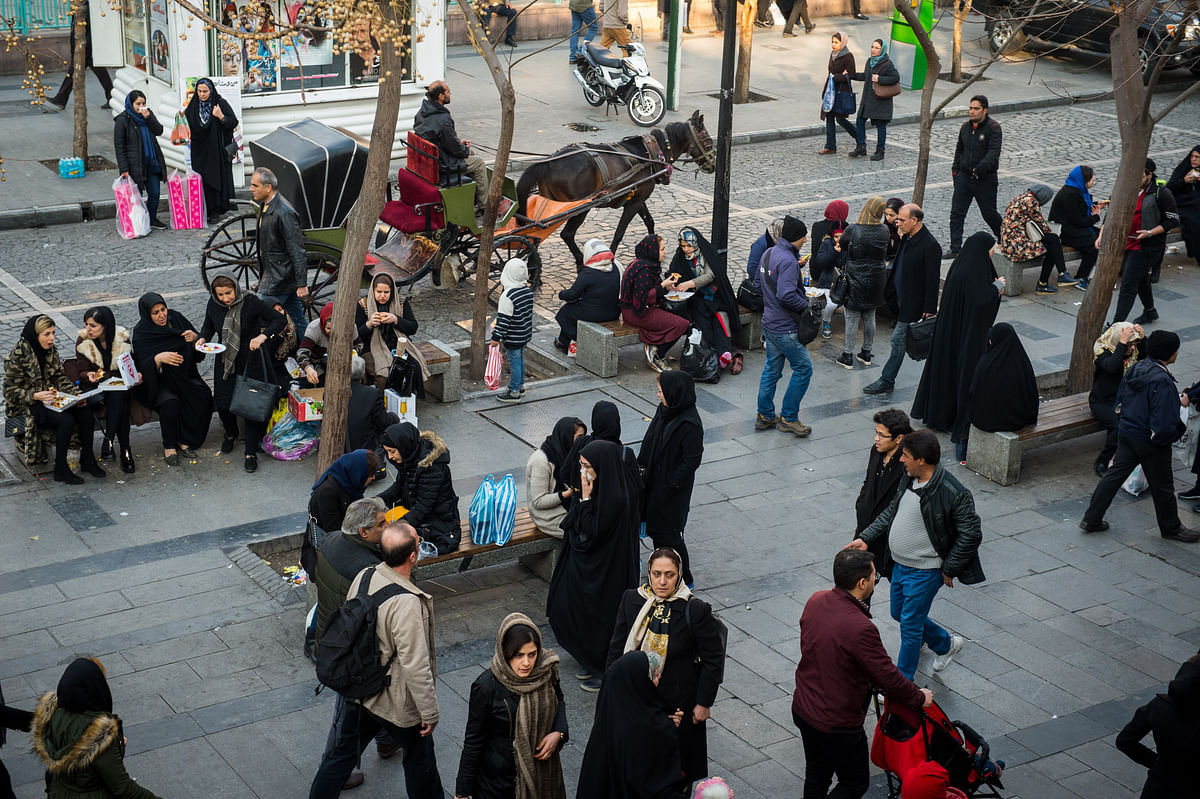 Pedestrians sit on public benches at a street in central Tehran, Iran, on  Jan. 8, 2018. (Photographer: Ali Mohammadi/Bloomberg)