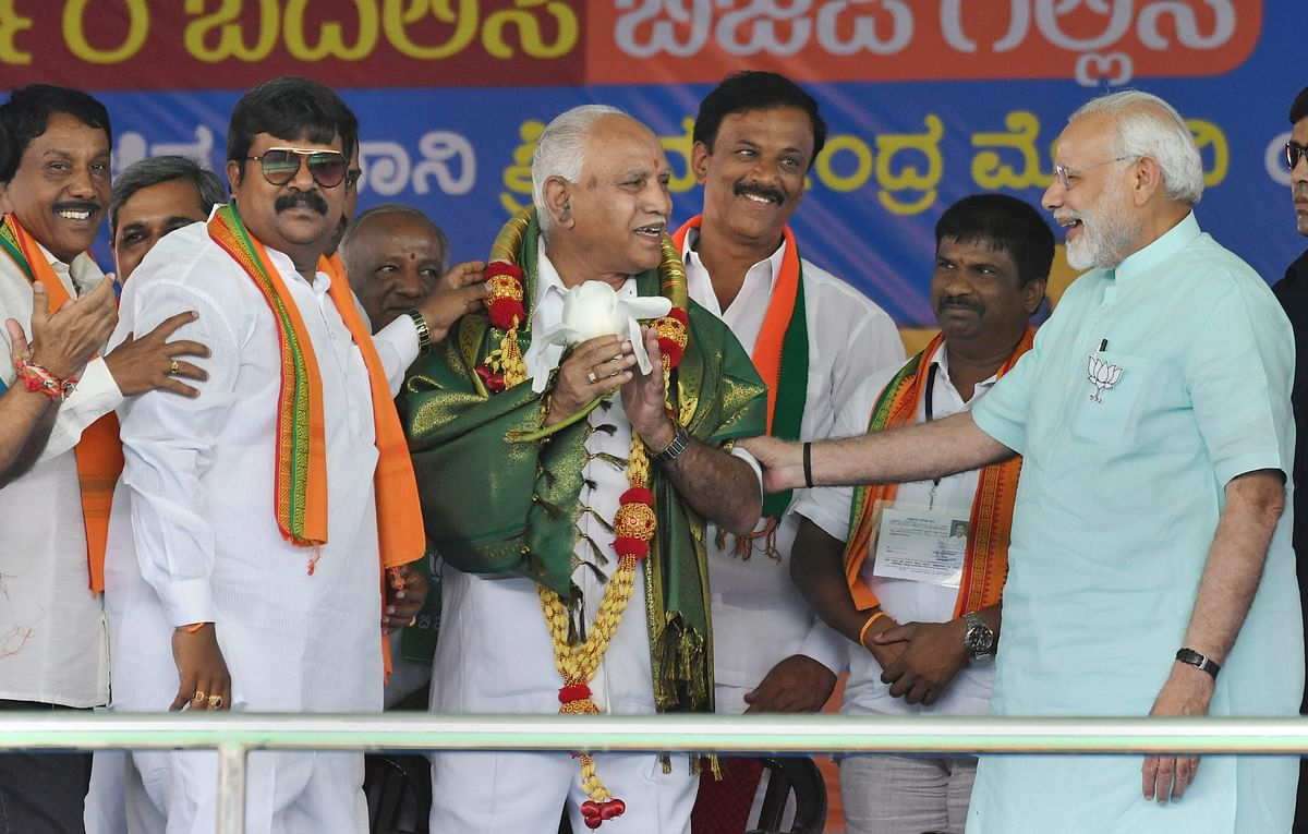 Prime Minister Narendra Modi and BJP's chief ministerial candidate BS Yeddyurappa share a lighter moment during Karnataka election campaign rally at Chamarajanagar on Tuesday. (Source: PTI)