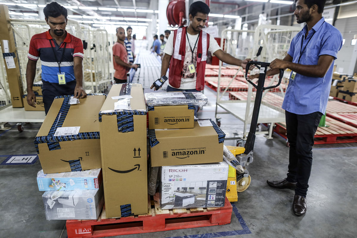 Employees prepare a cart stacked with packages at the Amazon fulfillment center in Hyderabad, India. (Photographer: Dhiraj Singh/Bloomberg)