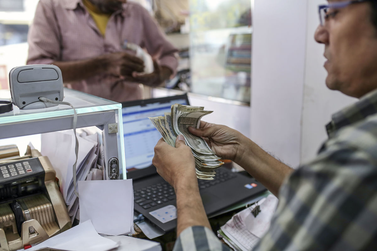 A cashier counts Indian rupee banknotes in the Byculla area of Mumbai, India, (Photographer: Dhiraj Singh/Bloomberg)