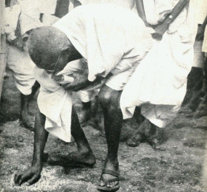 "Mahatma Gandhi picks up salt after the march to Dandi, Gujarat, on April 6, 1930. (Photograph: <a href=""https://twitter.com/narendramodi"">@<b>narendramodi</b></a>/Twitter)"