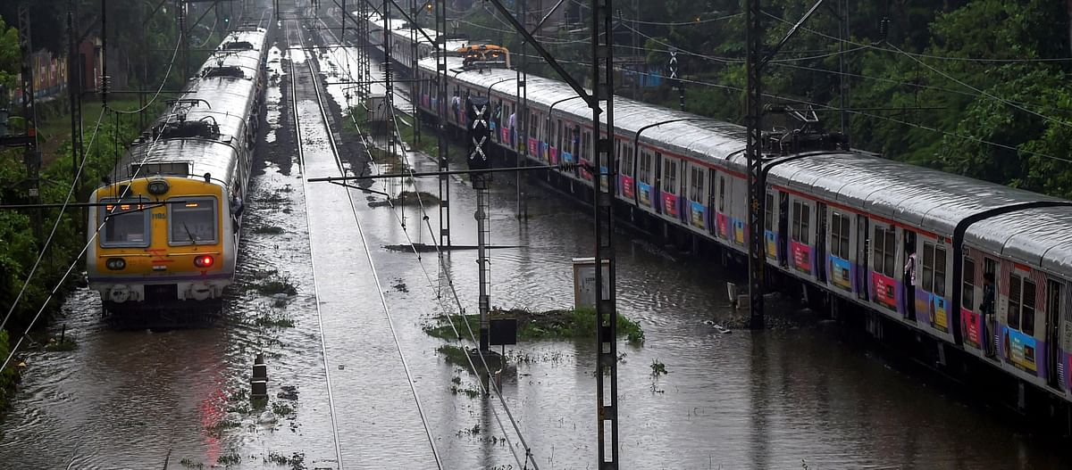 A train chugs on water-logged tracks during heavy rains, in Mumbai. (Source: PTI)