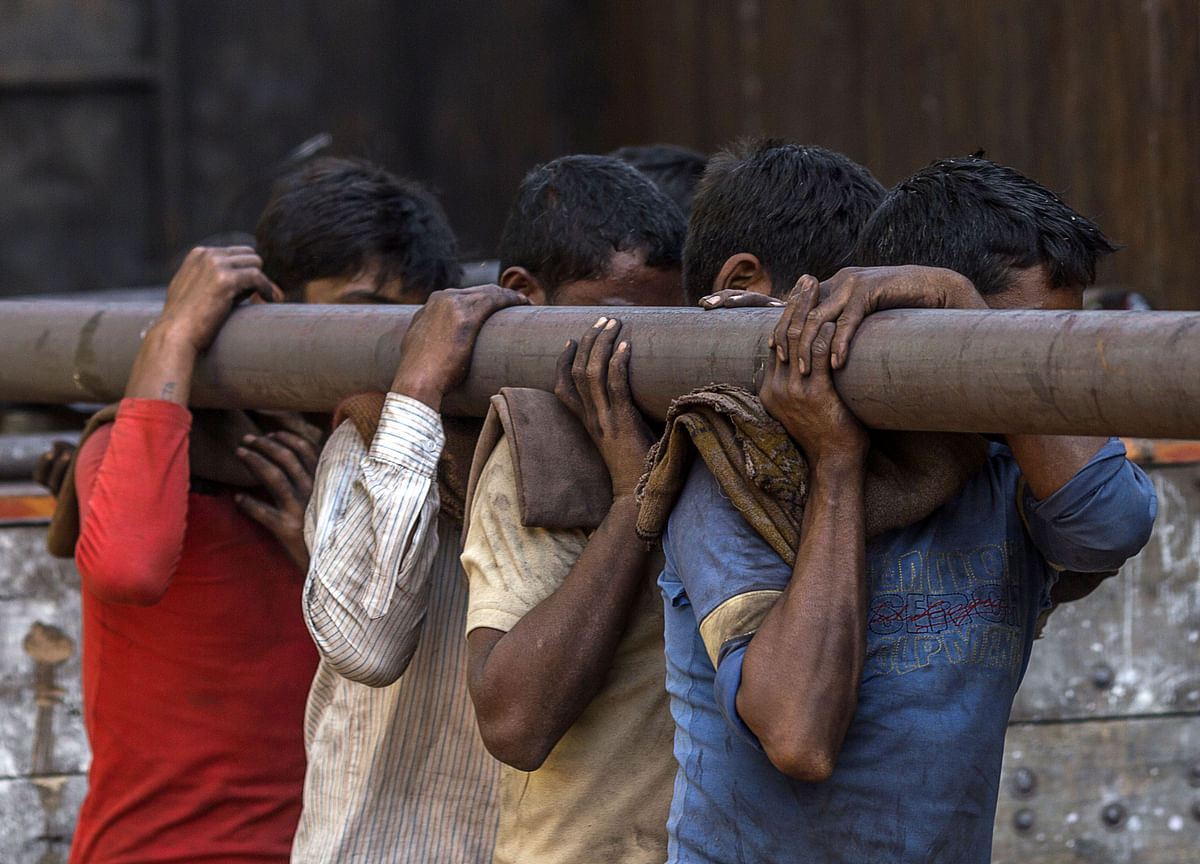Workers carry an iron pipe on their shoulders at a steel and iron market area in India. (Photographer: Prashanth Vishwanathan/Bloomberg)