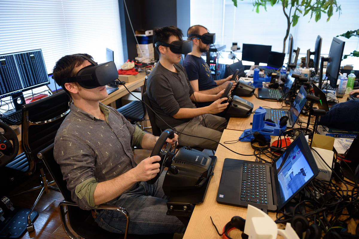 Employees wearing virtual reality headsets use Sony  PlayStation wheel controllers to perform maneuvers on virtual simulations in Tokyo, Japan, on March 16, 2018. (Photographer: Akio Kon/Bloomberg)