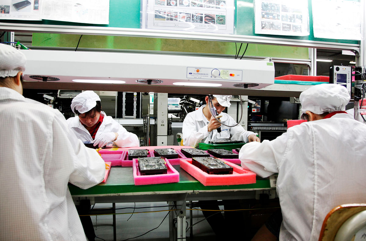 Employees work on the assembly line at Hon Hai Group's Foxconn plant in Shenzhen, Guangdong province, China. (Photographer: Qilai Shen/Bloomberg)