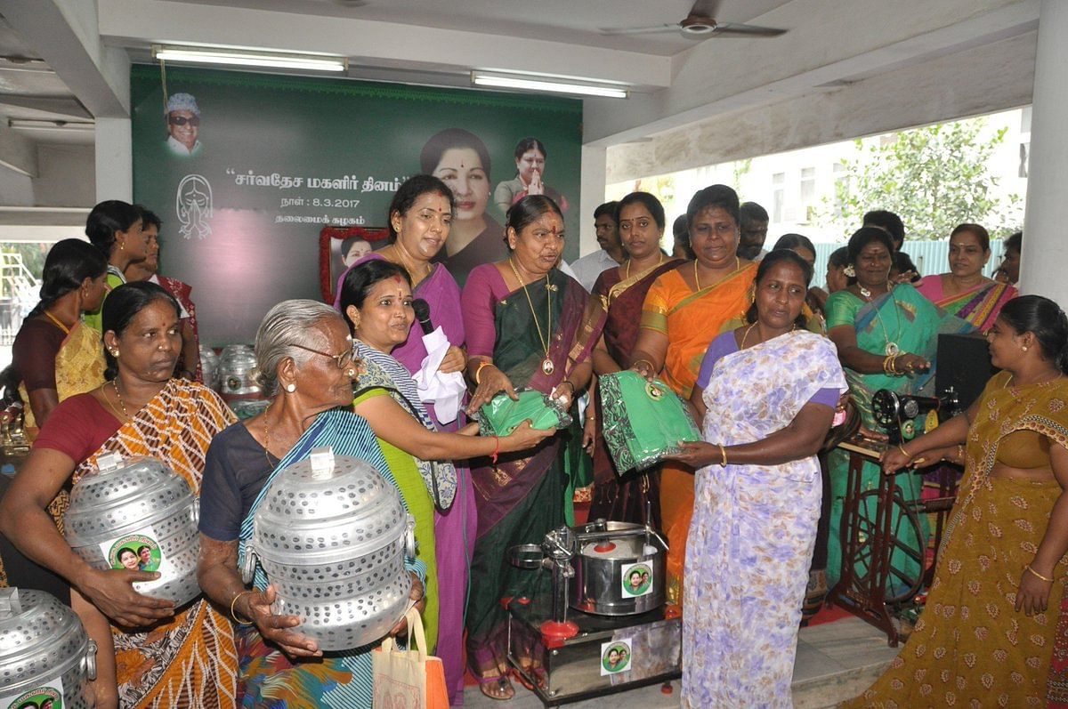 "AIADMK party workers hand out cookers, grain mixers, sarees, and sewing machines. (Photograph: Twitter/<a href=""https://twitter.com/AIADMKOfficial"">@<b>AIADMKOfficial</b></a>)"