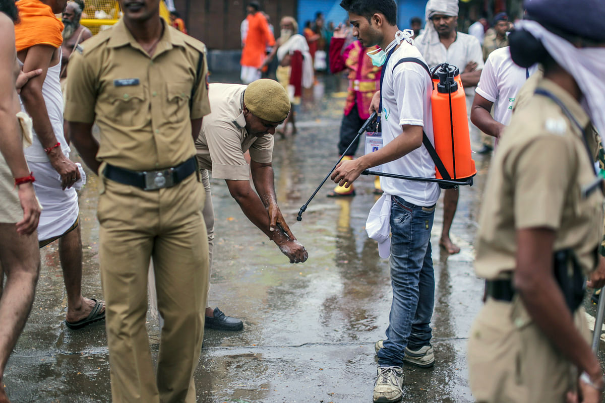 A street cleaner carrying a spray pack of disinfectant,  assists a police officer cleaning his hands in Nashik, Maharashtra, India. (Photographer: Dhiraj Singh/Bloomberg)