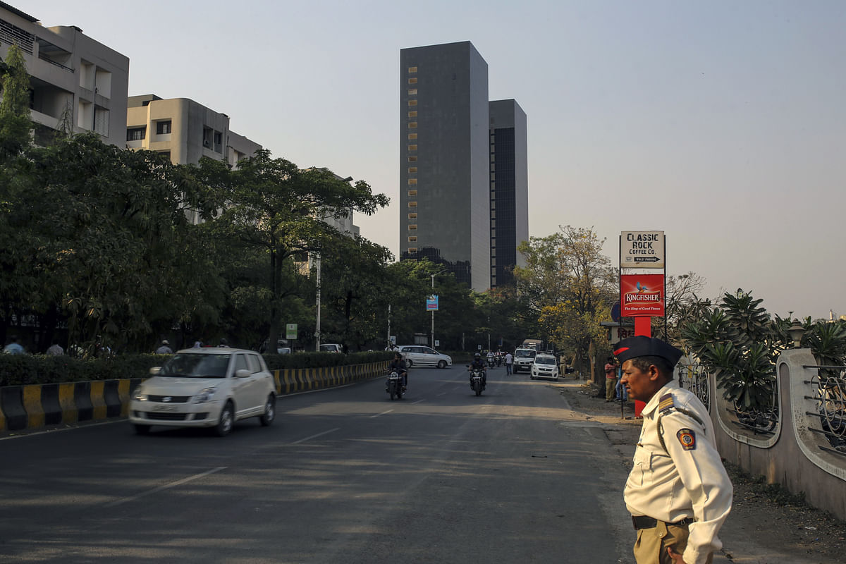 A police officer stands at the side of a road in Pune. (Photographer: Dhiraj Singh/Bloomberg)