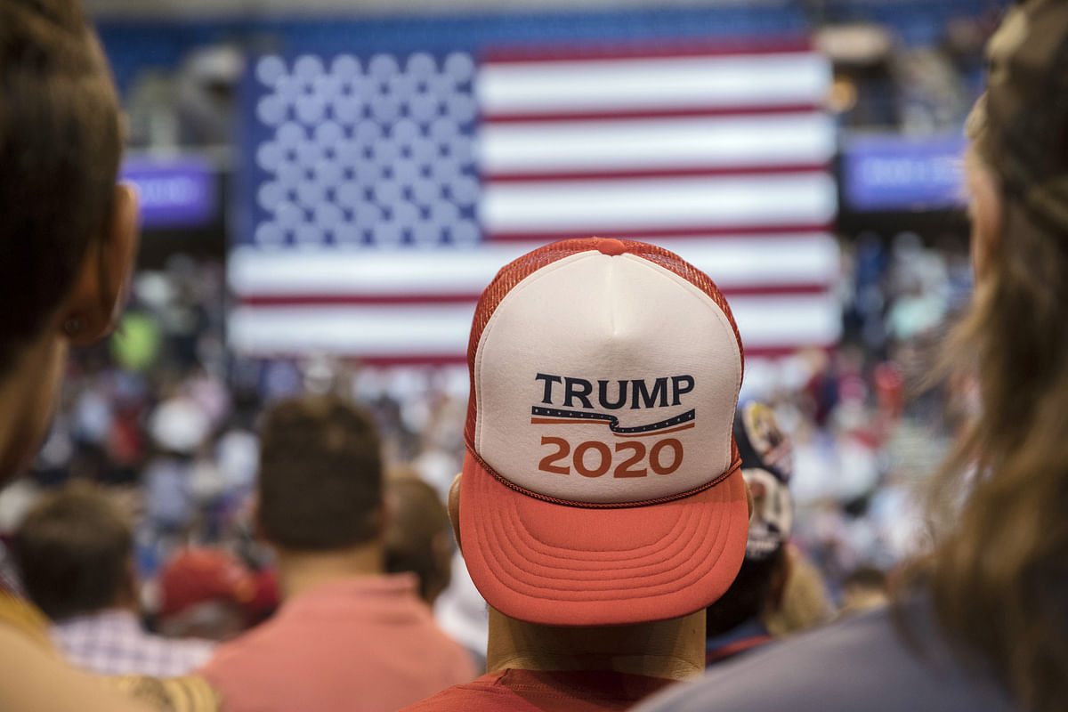 An attendee wears a 'Trump 2020' hat before the start of a rally with U.S. President Donald Trump in Wilkes-Barre, Pennsylvania, U.S., on Aug. 2, 2018. (Photographer: Victor J. Blue/Bloomberg)