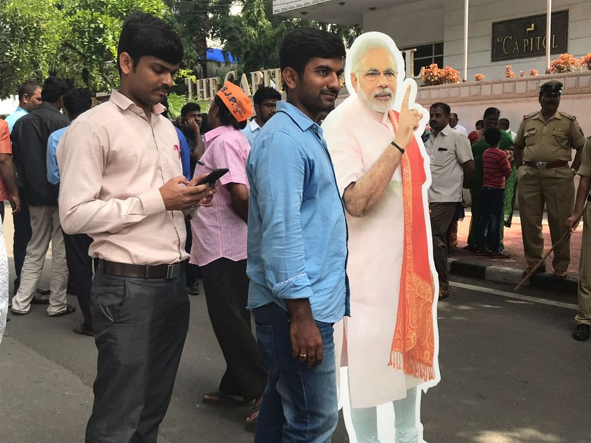 A BJP supporter holds a poster of Prime Minister Narendra Modi, in Karnataka, on May 16, 2018. (Photograph: PTI)