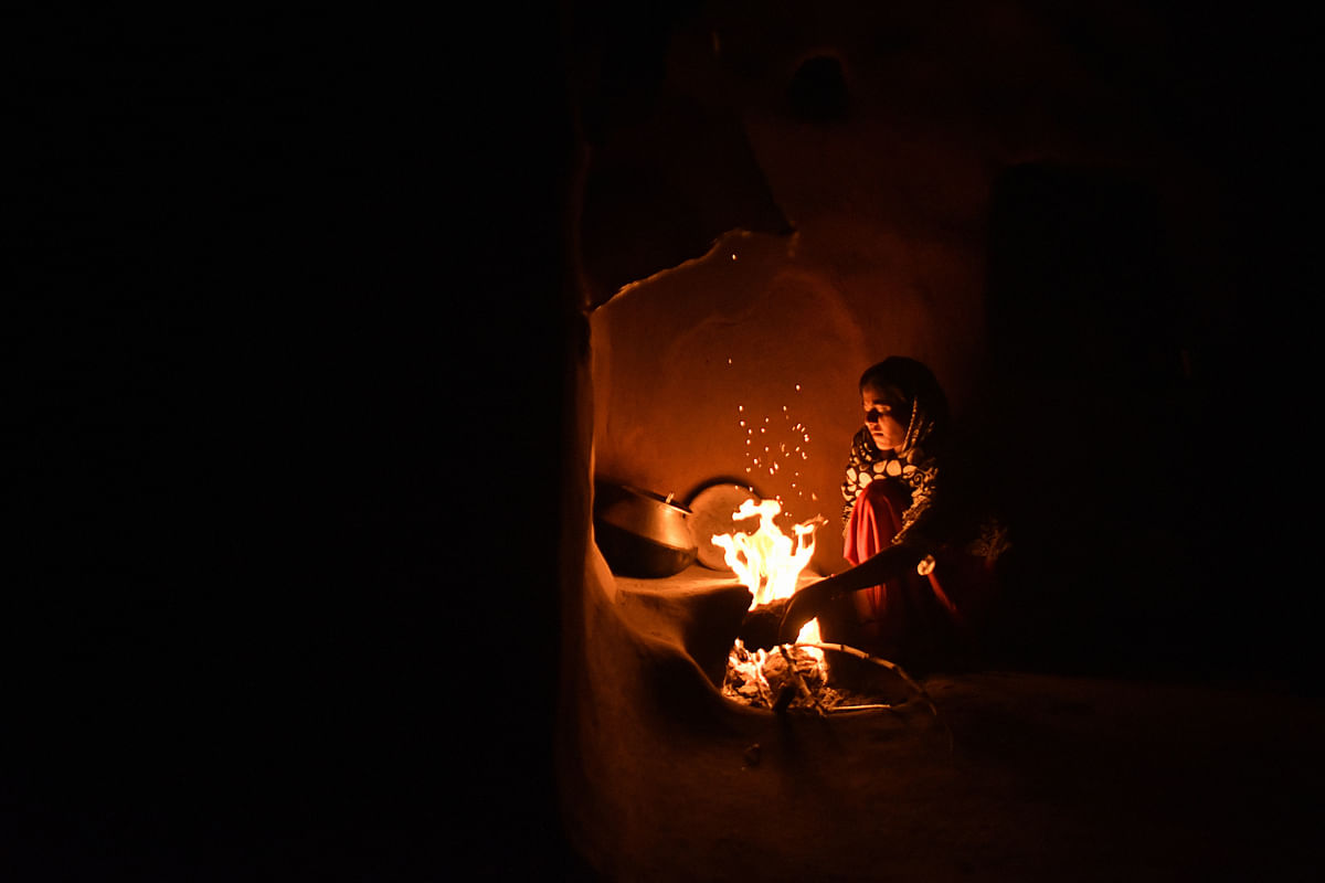 A woman cooks food by fire inside a home in  Rajasthan. (Photographer: Anindito Mukherjee/Bloomberg)