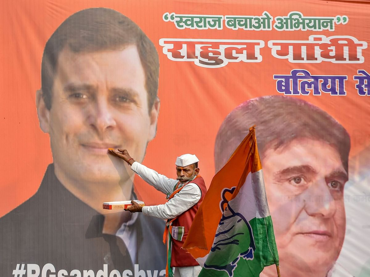 A Congress supporter offers sweets to a photo of  Rahul Gandhi, in Lucknow, on Dec. 11, 2018. (Photographer: Nand Kumar/PTI)