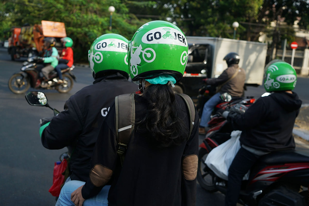 Go-Jek motorcycle taxi drivers and passengers travel through traffic in Jakarta, Indonesia. (Photographer: Dimas Ardian/Bloomberg)