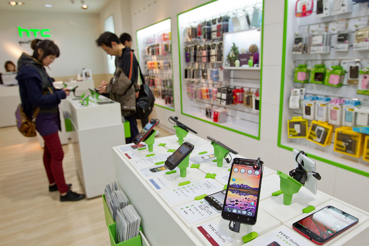 An  HTC smartphone, right, is displayed at one of the company's stores in Taipei, Taiwan. (Photographer: Maurice Tsai/Bloomberg)