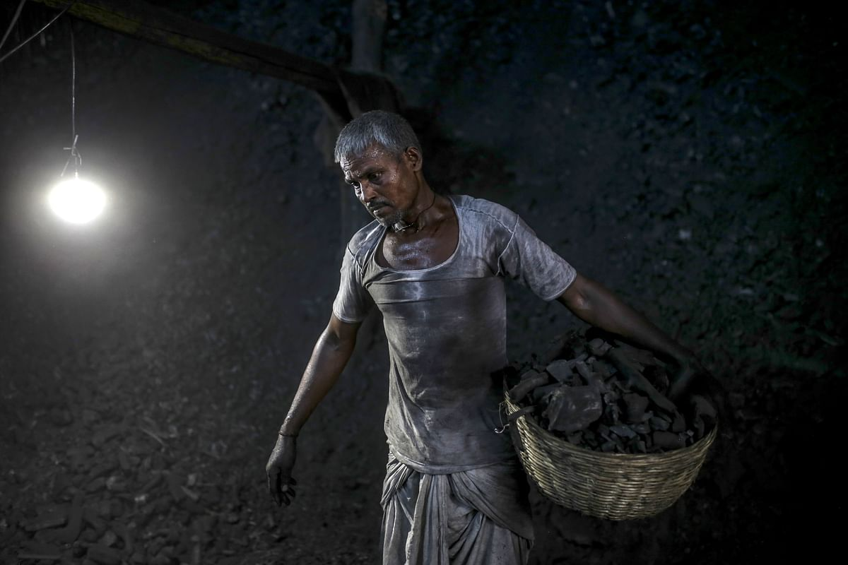 A worker carries a basket of charcoal at a coal wholesale market in Mumbai. (Photographer: Dhiraj Singh/Bloomberg)