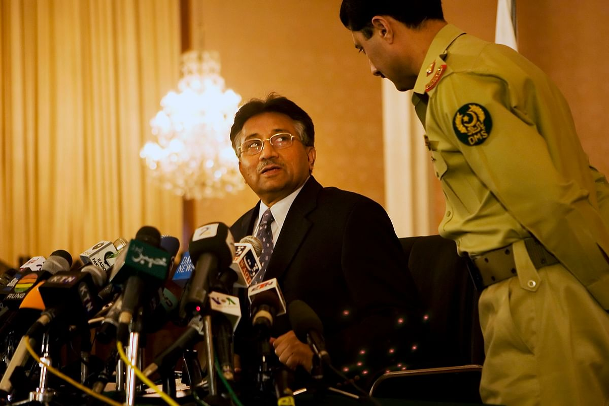 Then President of Pakistan General Pervez Musharraf speaks to an aide before the start of a news conference in Islamabad, Pakistan. (Photographer: Adam Ferguson/Bloomberg News)