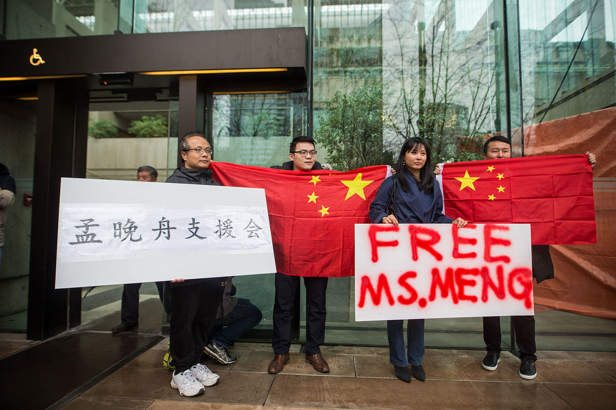 People hold signs and Chinese flags in support Meng Wanzhou, chief financial officer of Huawei Technologies, outside of a bail hearing at the Supreme Court in Vancouver, Canada, on Dec. 11, 2018. (Photographer: James MacDonald/Bloomberg)
