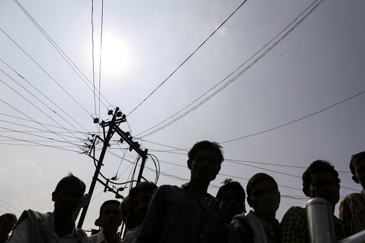 Residents of Dhadgaon village in Maharashtra under an electricity transmission pole and cables.  (Photographer: Dhiraj Singh/Bloomberg)