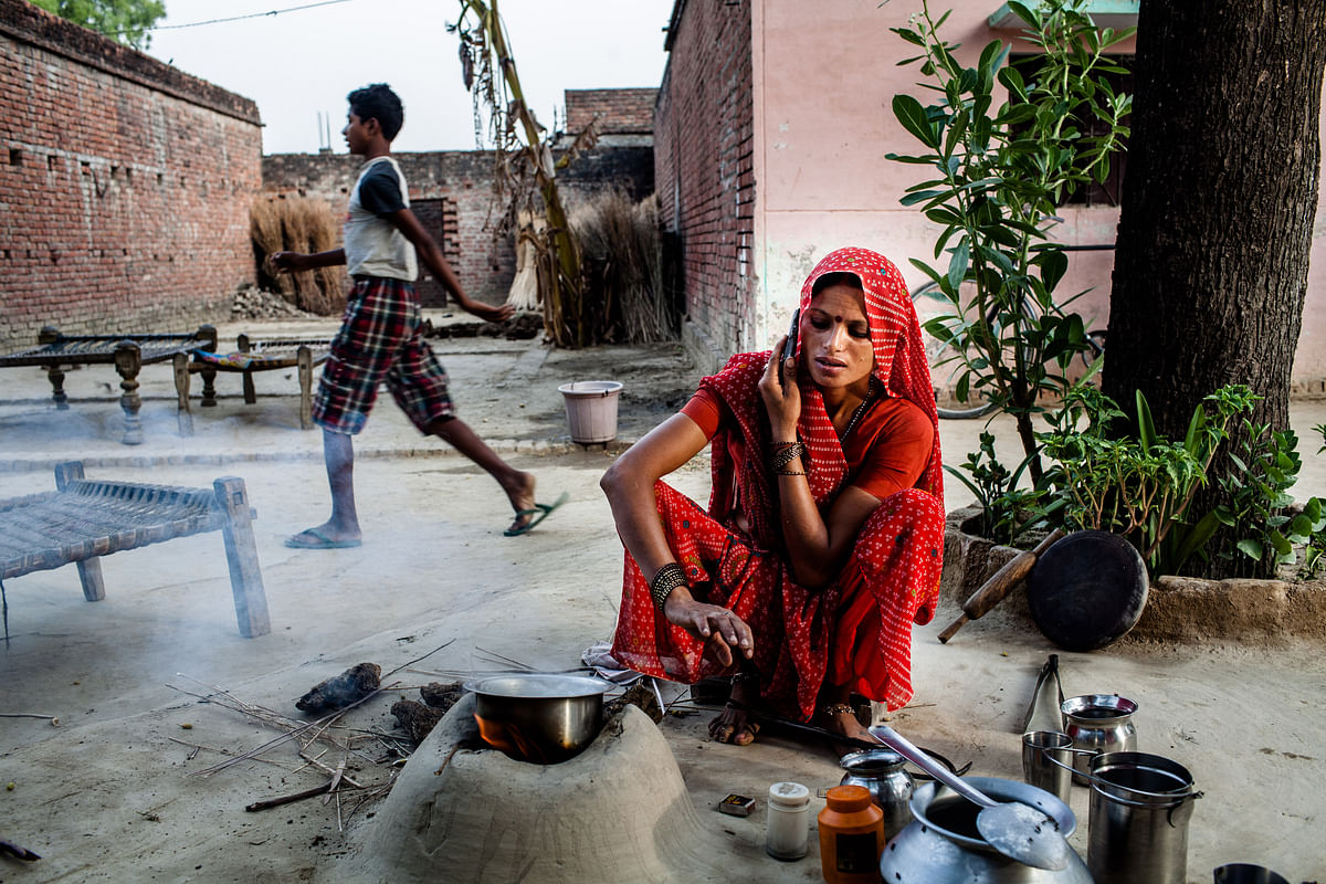 A resident of Pratapgarh district of Uttar Pradesh speaks on a mobile phone while she boils milk in an open kitchen. (Photographer: Sanjit Das/Bloomberg)