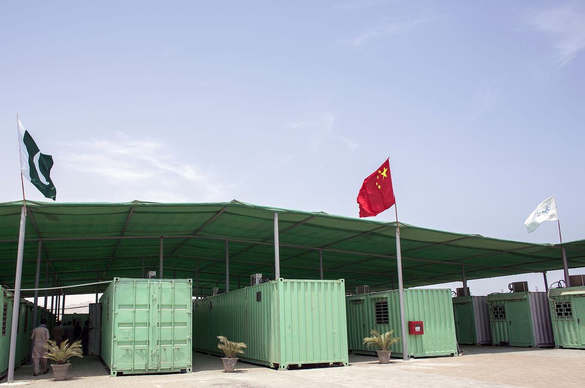 A Pakistani and Chinese national flag fly next to containers at a workers camp, operated by China Overseas Ports Holding Co., in Gwadar, Balochistan, Pakistan. (Photographer: Asim Hafeez/Bloomberg)
