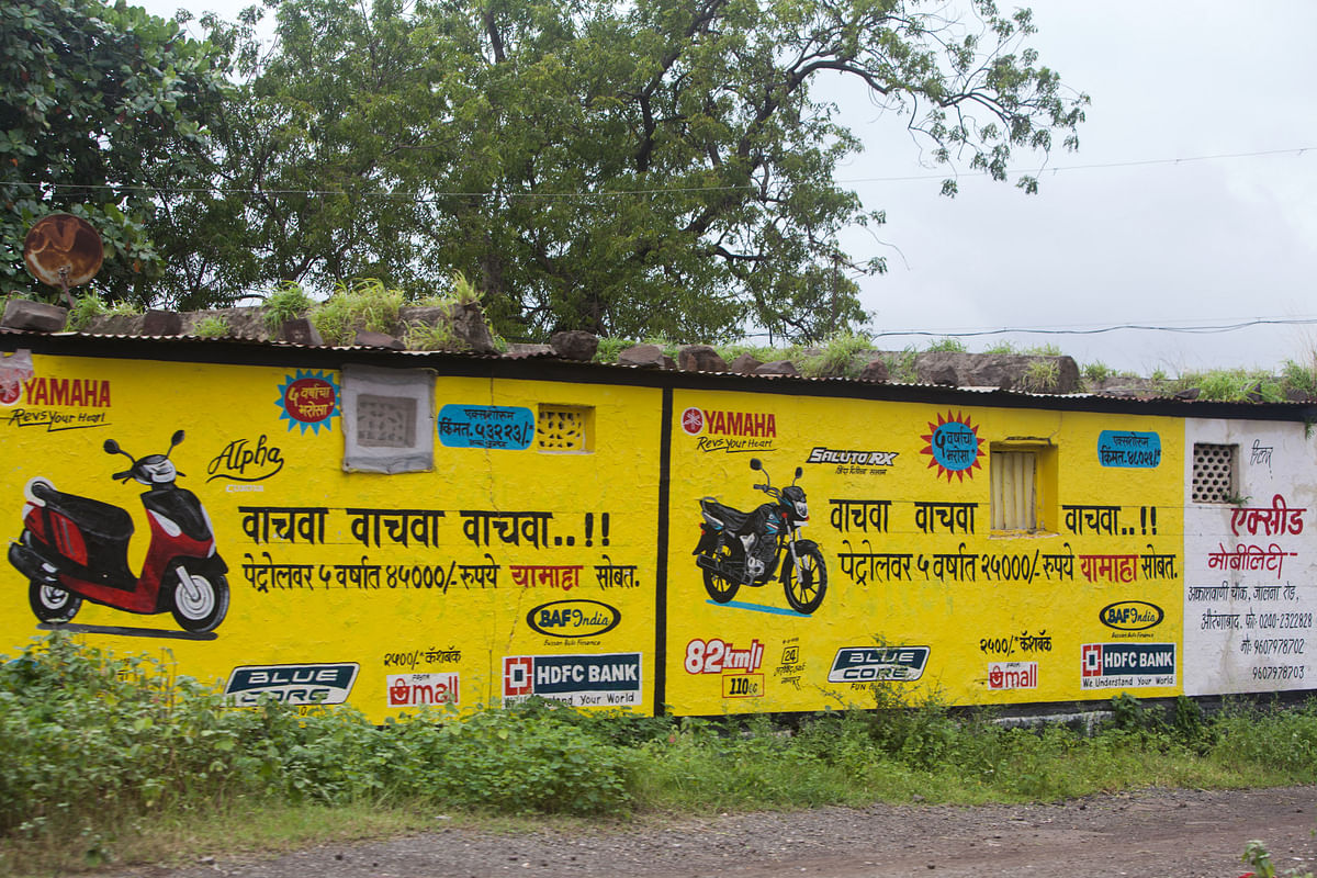 An advertisement for motorcycles is displayed on the side of a house in the village of Ghansoli, Maharashtra, India (Photographer: Karen Dias/Bloomberg)