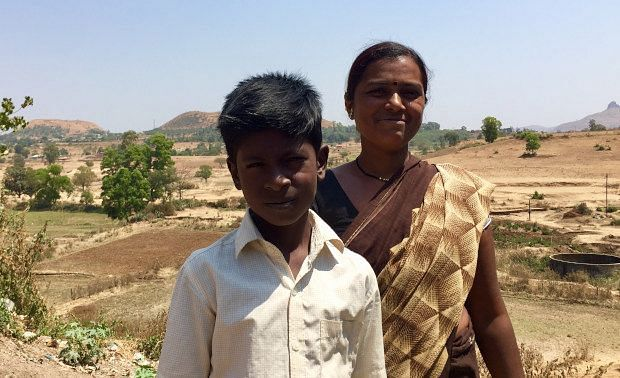Kamal Gangrude, 35, with her son in Pimplad village of Maharashtra's northwestern Nashik district. In the backdrop are the fields that used to provide a steady supply of farm jobs, but have now been sold to developers, thus restricting employment options for the village's poor. (Photographer: Tish Sanghera, IndiaSpend)